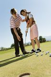 Man teaching teenage girl how to putt Stock Photo