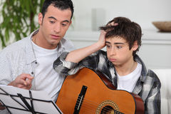 Man teaching son the guitar Stock Images