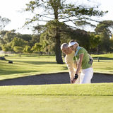 Man teaching a woman how to play golf Stock Images