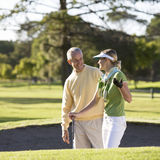 Man teaching a woman how to play golf Stock Photo