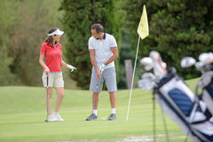 Man teaching woman how to play golf royalty free stock photography