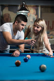 Man Teaching Woman How To Play Pool Royalty Free Stock Photography