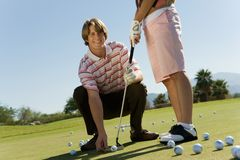 Man Teaching Woman To Play Golf royalty free stock photography