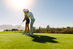 Man teaching woman to play golf on field stock image