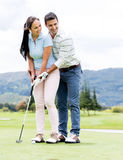 Man teaching woman to play golf Stock Photography