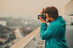 Man In Teal Button-Up Long Sleeved Shirt Shooting Using DSLR Camera Royalty Free Stock Photos