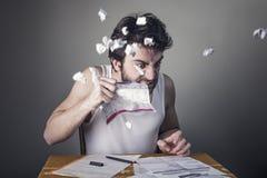 Man tearing apart bills. Man nervously tearing apart bills with his teeth royalty free stock image