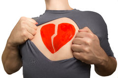 Man tearing apart grey t-shirt. Broken red heart painted on his Royalty Free Stock Image