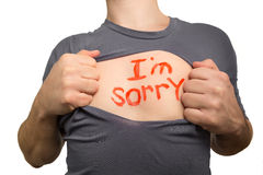 Man tearing apart grey t-shirt. Red text I am sorry written on h Stock Images