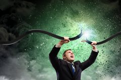 Man tearing cable. Determined businessman tearing electricity cable with hands Royalty Free Stock Image