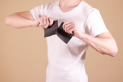 Man tearing a piece of paper in half blank black flyer brochure Royalty Free Stock Photos