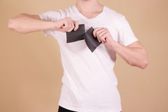 Man tearing a piece of paper in half blank black flyer brochure Stock Images