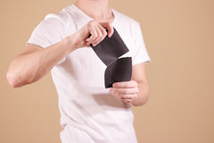 Man tearing a piece of paper in half blank black flyer brochure Stock Photography