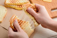 Man tearing a sandwich. With gooey melted cheese. Freshly made snack with yummy filling royalty free stock photography