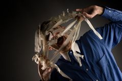 Man Tearing Tape from Face Stock Image