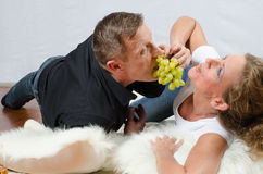 Man teasing woman with grapes Stock Images