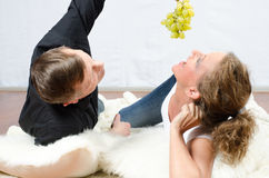 Man teasing woman with grapes Stock Photos