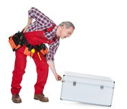 Man technician with back pain lifting metal box. Isolated on white background Royalty Free Stock Photo