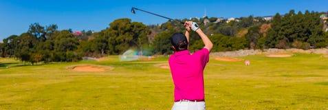 Man teeing av på en golfbana med en chaufför arkivbilder