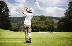 Man teeing-off golf ball. Male golf player teeing-off golf ball at beautiful golf course with forest stock images