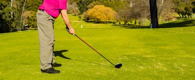 Man teeing off on a golf course stock photo