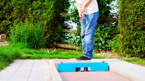 A man teeing off at miniature golf. The ball must pass through various obstacles to reach its destination stock photos