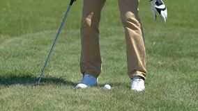 Man teeing up golf ball and preparing to make drive shot, starting to play stock video footage
