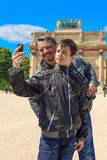 Man and teen in Paris take a selfie. In front of The Arc de Triomphe du Carrousel Royalty Free Stock Photo