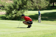 Man and Teenage Boy Golfing. Man wearing a red shirt back cap and shorts on the green of a golf course holding a club getting ready to putt with a teenage golfer Royalty Free Stock Image