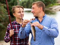 Man with teenager boy releasing fish from hook Royalty Free Stock Image