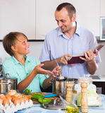 Man and teenager cooking together Royalty Free Stock Image