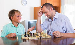 Man and teenager son playing chess Royalty Free Stock Images