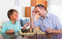 Man and teenager son playing chess Royalty Free Stock Image