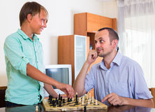 Man and teenager son playing chess Stock Image
