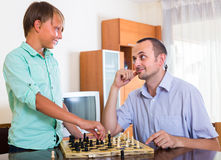 Man and teenager son playing chess. Smiling adult men and cheerful teenager boy playing chess at home royalty free stock images