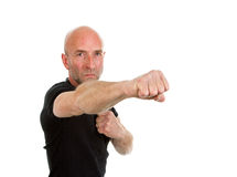 Man in teeshirt throwing a punch Stock Photo