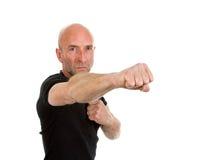 Man in teeshirt throwing a punch Stock Photo