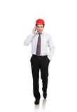 Man teknikern i en röd hjälm som talar på telefonen Fotografering för Bildbyråer