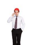 Man teknikern i en röd hjälm som talar på telefonen Arkivbild