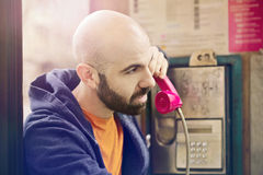 Man on a telephone booth Royalty Free Stock Image