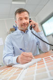 Man on telephone colour charts in front him Royalty Free Stock Photos