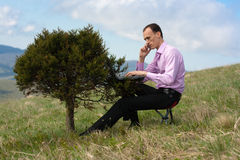 Man with telephone and computer on tree Royalty Free Stock Photo