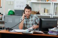 Man on telephone inside establishment. Man on the telephone inside establishment royalty free stock photo