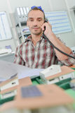 Man on telephone model houses in front him Royalty Free Stock Image