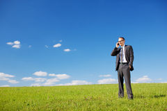 Man telephoning in a sunny green field. Businessman or manager using his mobile phone while standing in a sunny green field under a beautiful sunny blue sky with Stock Photo