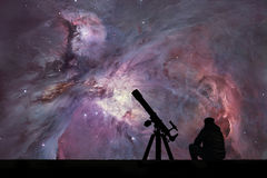 Man with telescope looking at the stars. The Orion Nebula. Messier 42 diffuse nebula in constellation Orion. Elements of this image are furnished by NASA stock photo