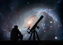 Man with telescope looking at the stars. Stellar Nursery NGC 1672. Spiral galaxy in the constellation Dorado.Elements of this stock images