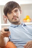 Man with television remote at home Royalty Free Stock Image