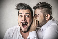 Man telling a secret to an other one Royalty Free Stock Image
