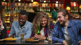 The man tells a joke in the company of friends sitting at the table. Girls and men laughing while sitting at a bar at a stock footage